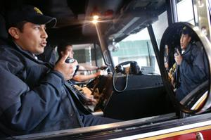 Primary view of object titled '[A fireman speaks with the dispatcher on the radio in his fire engine]'.