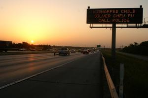 Primary view of object titled '[The sun sets over a highway with an Amber Alert sign]'.