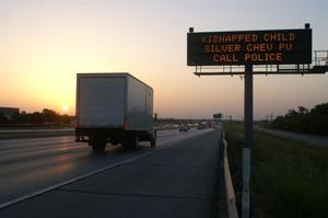 Primary view of object titled '[An Amber Alert message about a kidnapped child appears beside the highway]'.
