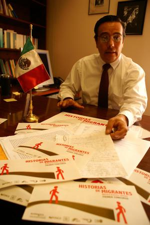 Primary view of object titled '[Oscar Solis Flores displaying letters and brochures on his desk]'.