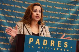 Primary view of object titled '[Lydia Gonzalez Welch speaking at podium with blue and yellow background]'.