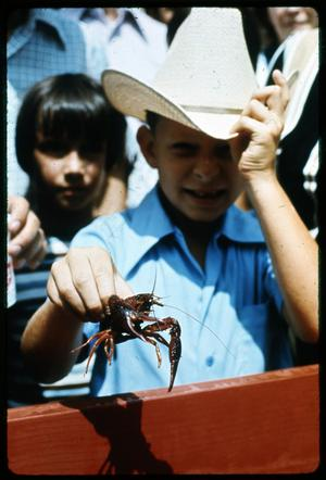 Primary view of object titled '[Boy Holding Crawfish]'.