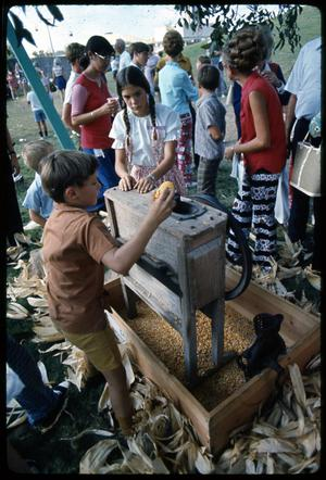 Primary view of object titled '[Children Learn How to Operate Antique Corn Sheller]'.
