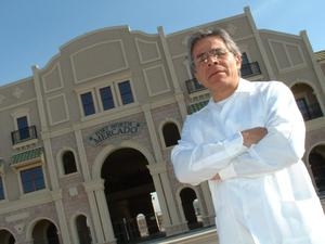 Primary view of object titled '[Jose Legaspi in front of building]'.