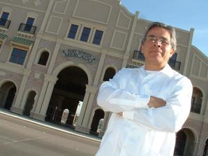 Primary view of object titled '[Jose Legaspi standing in front of building with arms crossed]'.