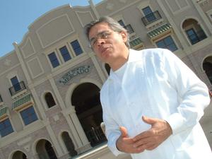 Primary view of object titled '[Jose Legaspi standing in front of Fort Worth Mercado]'.