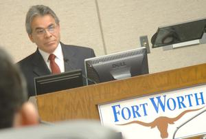 "Primary view of object titled '[Jose Legaspi standing behind podium with ""Fort Worth"" sign]'."