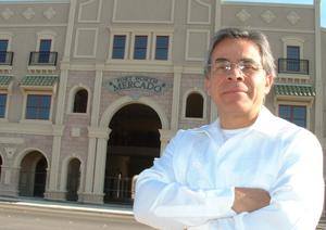 Primary view of object titled '[Jose Legaspi standing with arms crossed in front of Fort Worth Mercado]'.
