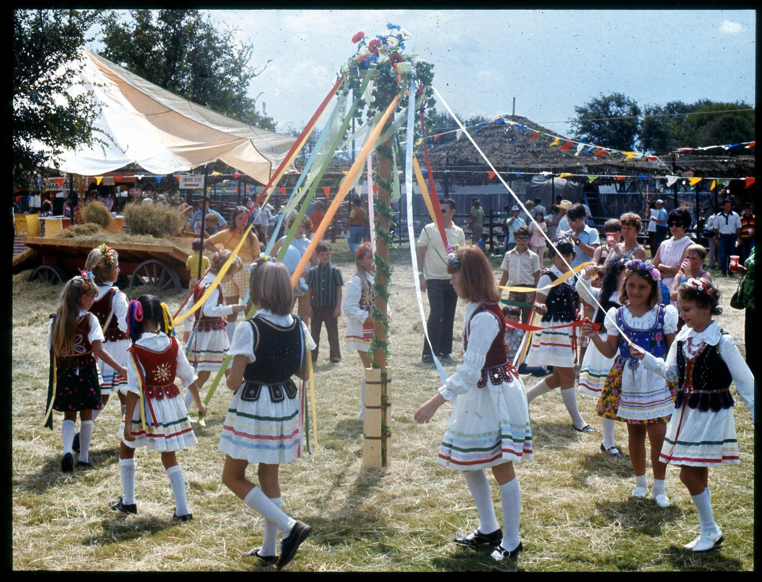 [Polish Children Around the Maypole], Photograph of Polish children dancing around the maypole at the Texas Folklife Festival. The maypole is erected outdoors in a grassy clearing. It is decorated with leafy garland spiraling up to the top where red, white, and blue flowers are displayed. Colored ribbons stream from the top of the pole down to the hands of the children walking clockwise around the pole. All of the children are girls, wearing white knee-high socks and white dresses with horizontal colored stripes near the hem. Over their dresses they are wearing red, black or blue vests embroidered with gold or silver decoration. Flowers or ribbons adorn each of their heads. A few people are standing in the background, watching.,