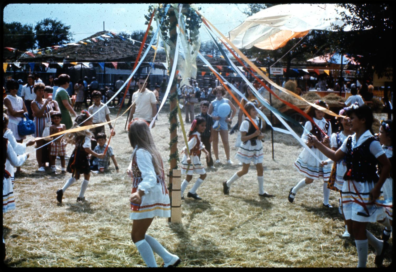 [Polish Children Dancing Around the Maypole], Photograph of Polish children dancing around the maypole at the Texas Folklife Festival. The Maypole is erected outdoors in a grassy clearing. It is decorated with leafy garland spiraling up to the top where red, white and blue flowers are displayed. Colored ribbons stream from the top of the pole down to the hands of the children running clockwise around the pole. All of the children are girls, wearing white knee-high socks and white dresses with horizontal colored stripes near the hem. Over their dresses they are wearing red, black or blue vests embroidered with gold or silver decoration. Flowers or ribbons adorn each of their heads. In the background, a few spectators are visible, as are pennant flags and other festival booths.,