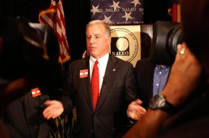 Primary view of object titled '[Howard Dean gesturing in front of NALEO seal]'.