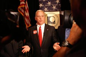 Primary view of object titled '[Howard Dean standing in front of NALEO seal with hands outstretched]'.