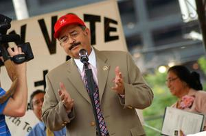 Primary view of object titled '[Hector Flores speaking at microphone wearing suit and red hat]'.