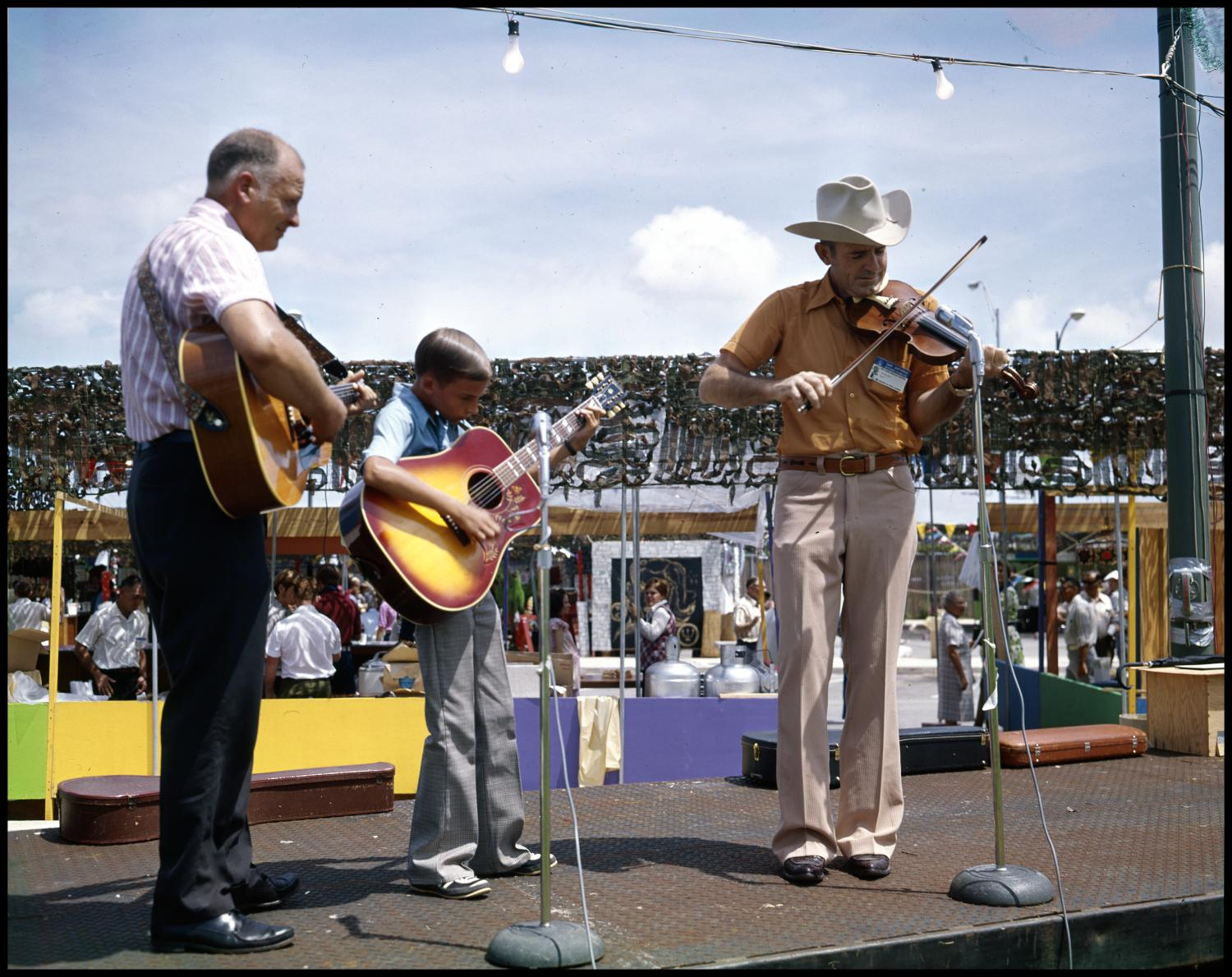 [Musicians Performing on Stage], Photograph of fiddler, Garland Gainer, playing with guitarists, Keith Worrell (center) and Vernon Worrell, at the second annual Texas Folklife Festival. The musicians are performing on a flatbed trailer and are standing in front of two microphones. Festival booths and participants are seen in the background.,