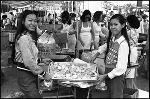 Primary view of object titled '[Two Women display food from a Chinese Food Booth]'.