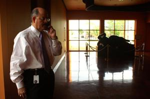 Primary view of object titled '[Hector Flores speaking on cellular phone with large windows in background]'.