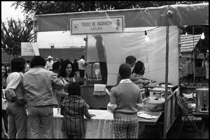 Primary view of object titled '[Tacos De Barbacoa Booth Serving Food]'.