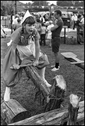 Primary view of object titled '[Dutch Girl Seesawing at the Texas Folklife Festival]'.