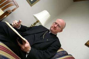 Primary view of object titled '[Bishop Kevin Vann sitting on sofa with book and pen]'.