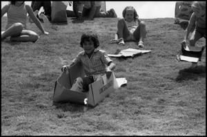 Primary view of object titled '[Child Sliding Down Hill at the Texas Folklife Festival]'.
