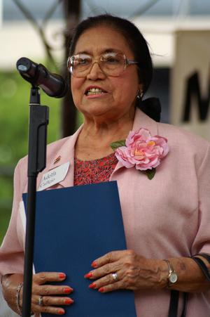 Primary view of object titled '[Adelfa Callejo holding blue folder and speaking into microphone]'.