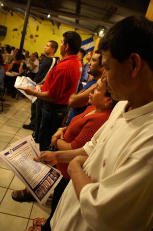 [A man holds printed material during a speech at the El Salvador Restaurant]