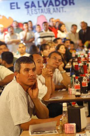 Primary view of object titled '[Men listen to a speaker in the El Salvador Restaurant]'.