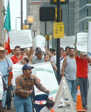 [Protesters carry signs and the Mexican Flag]
