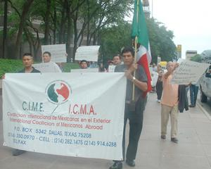 [Protesters carry banners, signs, and a Mexican Flag]