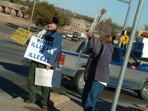 Primary view of object titled '[Two protesters holding signs]'.