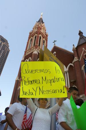[Female protester with sign next to Cathedral Santuario de Guadalupe in Dallas]