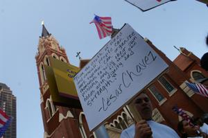 Primary view of object titled '[Male Protester With Sign Marches Past Cathedral Santuario De Guadalupe in Dallas]'.