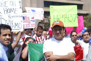 Primary view of object titled '[Protesters carry signs and a Mexican flag]'.