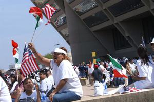 Primary view of object titled '[A woman raises a United States and Mexican flag in front of Dallas City Hall]'.
