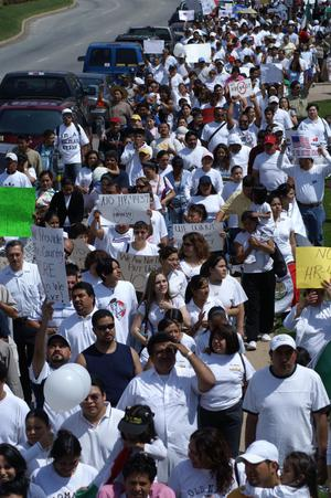 Primary view of object titled '[Protesters in white shirts carry signs]'.