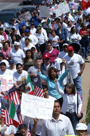 Primary view of object titled '[Marchers wear white shirts and carry the flags of the United States and Mexico]'.