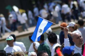 Primary view of object titled '[The flag of El Salvador is held up during march]'.