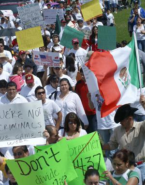 [Protesters carry signs and a Mexican flag]