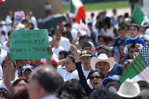 Primary view of object titled '[Protesters hold up Mexican and American flags and signs]'.