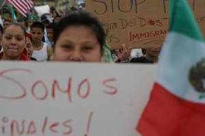 [Close-up on crowd with handwritten signs and Mexican flag]