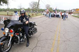 Primary view of object titled '[Police officer on motorcycle in front of group of protesters]'.