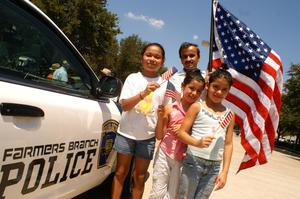[Man with a big U.S. flag and three girls with little U.S. flags stand beside a police car]