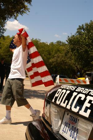 Primary view of object titled '[Man with a U.S. flag walks past a police car]'.