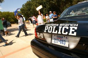 [Protesters with signs and flags march past a Farmers Branch police car]