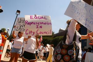 "[Protesters carry signs saying, ""United We Stand,"" and ""Equal Representation in City Council""]"