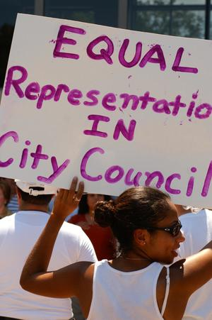 "[Protester holds a sign, ""Equal  Representation in City Council""]"