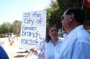 "[Protester holding a sign, ""Is the city of Farmers Branch racist?""]"