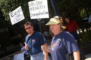 Primary view of object titled '[Two anti-immigration protesters with signs]'.