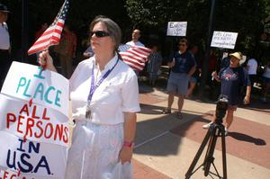 Primary view of object titled '[Several anti-immigration protesters with signs and U.S. flags]'.