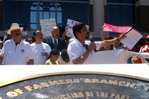 Primary view of object titled '[Speaker with a microphone, waving his arm, and protesters behind him]'.